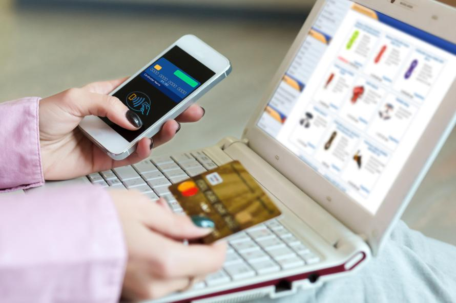 Hands of Woman shopping on-line holding credit Card and Telephone